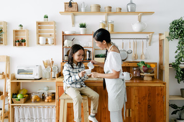 Mother and kid drinking tea together in the kitchen