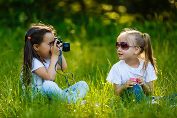 Two children girl(female, woman) hold a camera take a picture each other(together) with smile(happy)