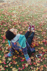 Girl in Autumn leaves with her phone