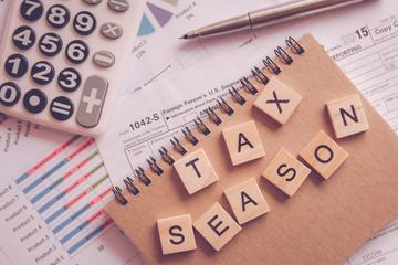 Tax season with alphabet letter wooden blocks tiles  on U.S. tax form