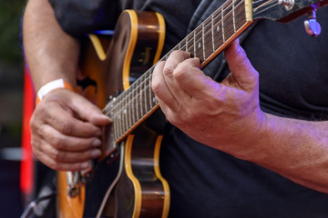 Detail of guitarist's hands and his black electric guitar at an outdoor jazz presentation