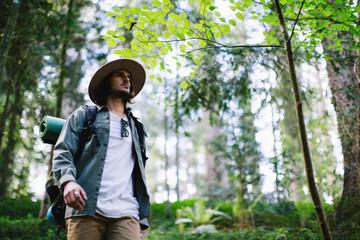 Hiker wearing backpack walking in the woods.