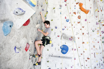 Young rock climber training on an indoor climbing wall