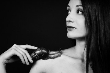 Black and White Portrait of Attractive Young Girl with Big Snail on Shoulder on in Studio. Cosmetological Procedure. Spa Concept
