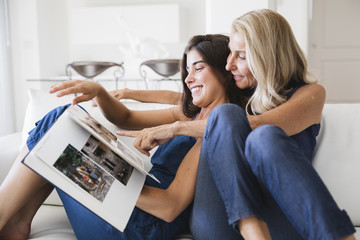 Happy mother and daughter looking at a photo album together
