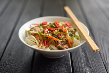 Traditional Asian noodles minimalist style. Stir fry udon noodles with meat, vegetables, chili and spring onion on burnt black background