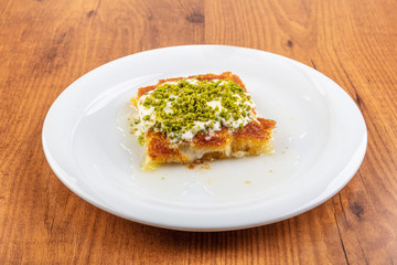 Turkish dessert kunefe on kaymak, cream slide with pistachio powder