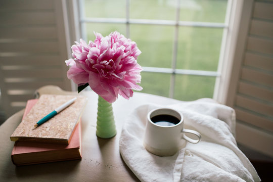 journal, book, coffee, and a flower on a desk with copy space