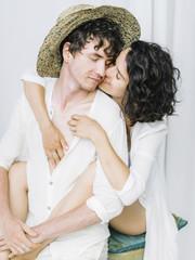 Tender couple in white kissing