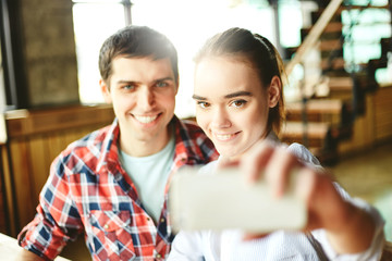 Young boy and girl sitting at table together and using phone to take selfie