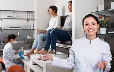 friendly woman nail technician welcoming to modern beauty salon