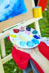 paints, brush, palette, female hand of the artist