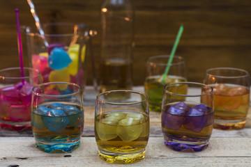 Vasos con whisky , cubitos de hielo de colores
