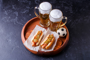 Photo on top of two glasses of beer and hot dogs on wooden tray with football