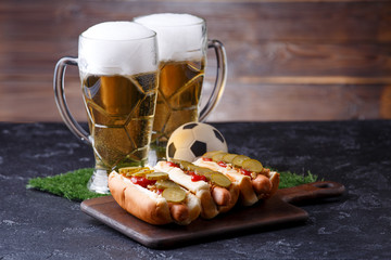 Photo of two mugs of foam beer, green grass with football, hotdogs