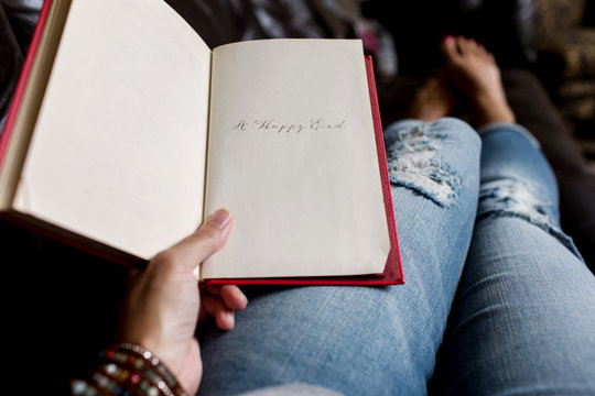 """woman holding a book with """"""""A Happy End"""""""" written on the last page"""