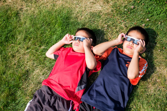 Asian Kids Looking at Solar Eclipse Using a Solar Lens Glasses