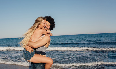 Multi-ethnic couple having fun at the beach
