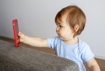 Cute little baby taking selfie holding smartphone in his hand, child and gadget concept, new generation, parent control