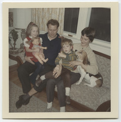 Vintage family photo with pet beagle dog on a sofa a living room