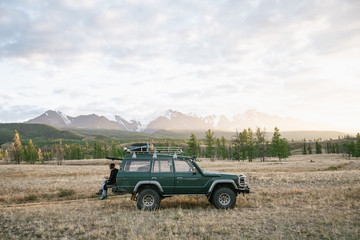 Two anonymous men sitting on the green jeep parked in the wild area surrounded by mountains