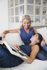 Happy mother and daughter looking at a photo album together on the sofa
