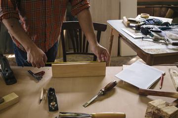 Young carpenter measuring timber