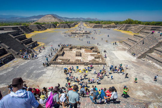 View of the Sun Pyramid and the Alley of Death - City of Teotihuacan Mexico - Ancient Maya Pyramids with people climbing the steps of Moon Pyramid.