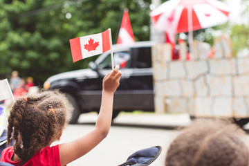 Portrait of child happily waving a Canadian flag at a Canada day parade