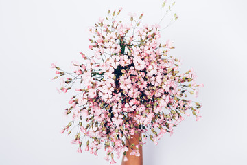 Female's hand holding bouquet of pink wildflowers