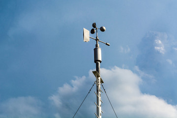 Professional wind weather vane and cloudy dramatic blue sky in weather station. Meteorology concept.  Automatic weather station for monitoring ambient air pressure, humidity, wind speed and direct