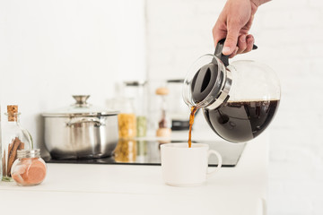 cropped image of man pouring coffee into cup from coffee maker at kitchen