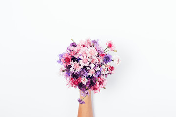 Woman's hand giving small bouquet of colorful cornflowers