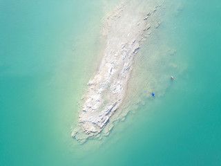View from a drone: white rocky island and two man bathing surrounded by blue water