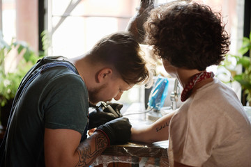 Master making hand tattoo in studio