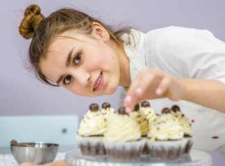 Young happy woman decorates cupcakes at kitchen