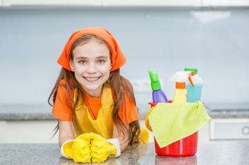 Happy little girl with cleaning supplies in bucket at kitchen