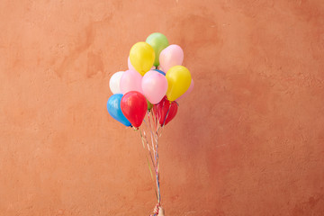 Colorful balloons on orange background