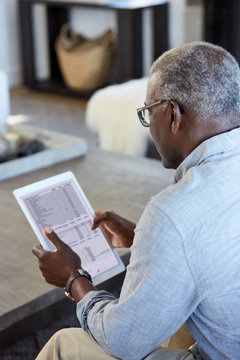 African American Senior man looking at a financial budget spreadsheet on a large digital tablet