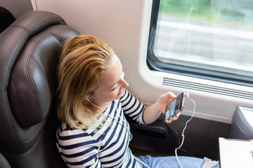 Woman communicating on cellphone using headphone set while traveling by train in business class seat.