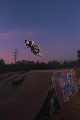 Teenager with BMX jumping in midair on wooden ramp