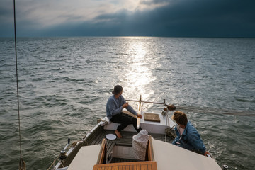 Two adventurous on a sailboat sailing the sea