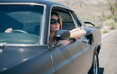 Woman with arm out cruising in the desert