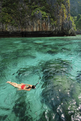 A asian female tourist in a red swimsuit is enjoying Maya Bay.