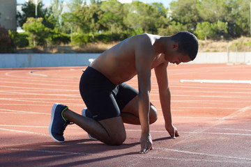 Young african american athlete positioning for the race in the track and fields