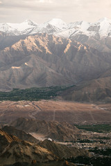 Panoramic shot of mountain range with snowy peaks  in sunset light