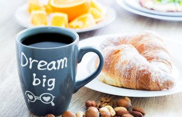 Dream big. Good morning breakfast. Mug of coffee with croissants, nuts and oranges