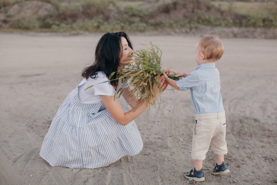 Side view portrait of lovely moment when the little boy giving a bouquet of wild flowers to his mom