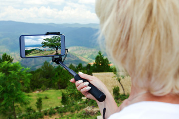 Female traveller make a panoramic photo from the mountain to her phone for Instagram or other social networks. Travel concept. Summer vacation.