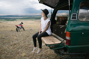 Young tattooed woman sitting in old jeep parked in the wild area surrounded by mountains